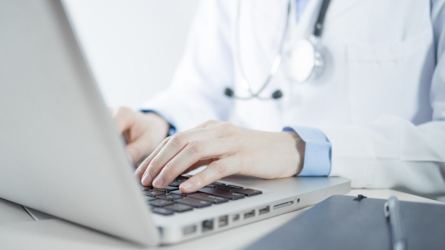 Female doctor working with laptop computer in her office for electronic medical record